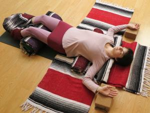 yoga student laying on blankets with arms out