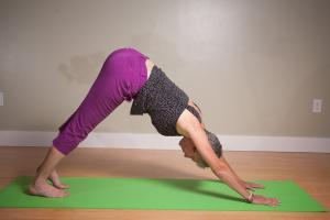 yoga teacher doing a v shaped yoga pose with hands and feet