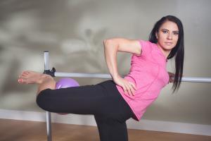 svetlana holding bar with one leg at 90 degrees holding ball on back of leg
