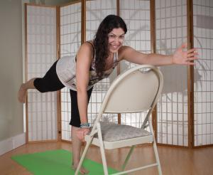 lisa with one hand on chair doing yoga warrior pose