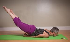 laurel yoga pose with chest on a yoga mat and legs in the air