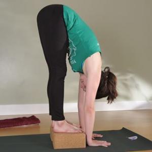 colleen lyons standing on yoga block bent over touching yoga mat