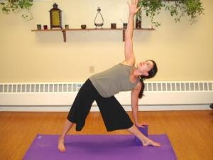 lisa on a purple yoga mat doing pose touching toes and looking up